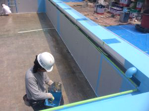 プールの防水加工作業中