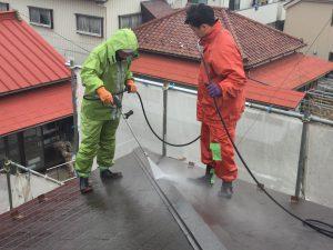 屋根の高圧洗浄をする職人達